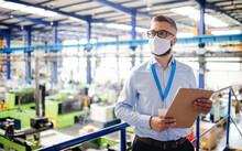 Technician Or Engineer With Protective Mask Working In Industrial Factory, Standing.