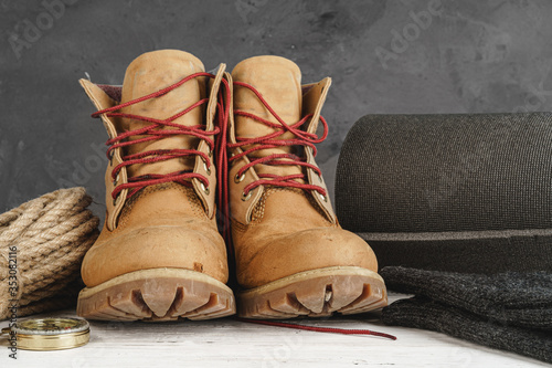 Fototapeta Hiking boots and rope hank on wooden board obraz