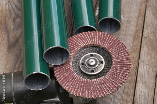 Steel pipes, angle grinder with mounted grit flap discs Fototapete