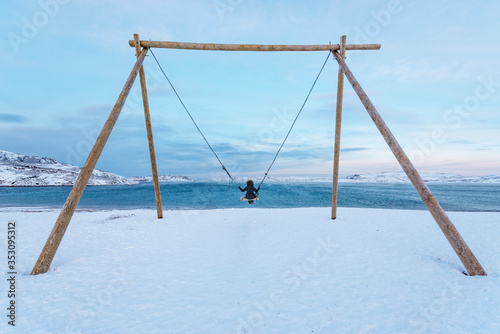 фотография A girl swings on a huge swing on the beach in winter against the background of t