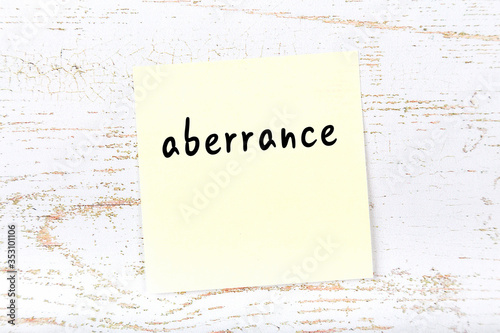 Yellow sticky note on wooden wall with handwritten word aberrance Canvas Print