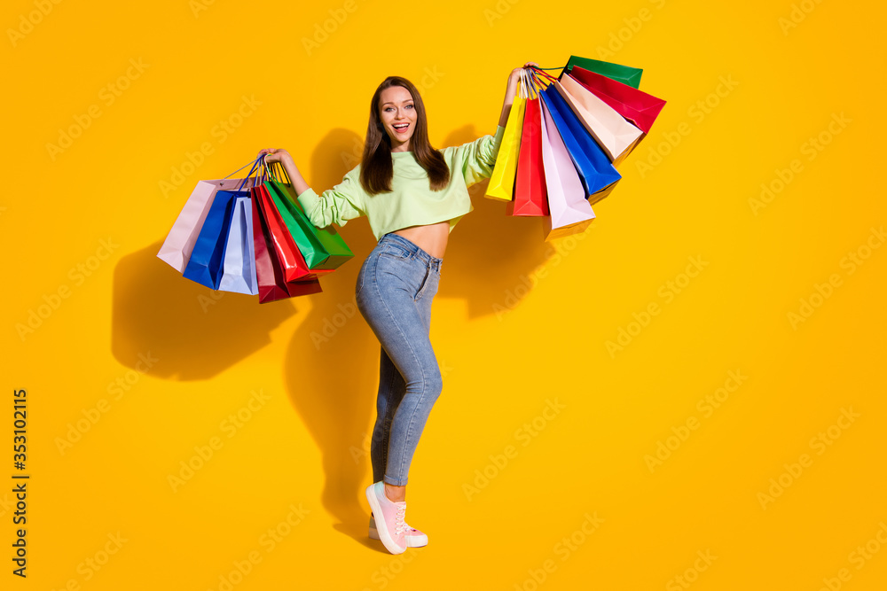 Fototapeta Full length photo of pretty shopaholic lady good mood street look hold many shopping bags wear green cropped sweatshirt jeans shoes isolated vivid bright yellow color background