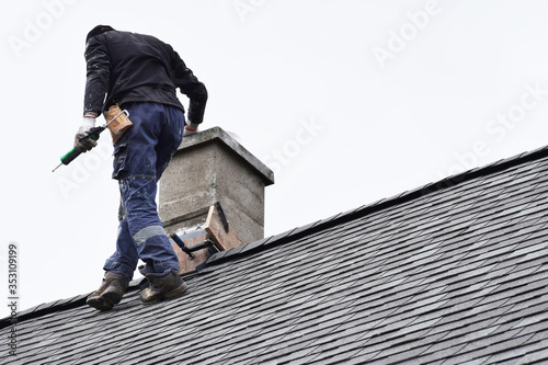 Tablou Canvas Roofer construction worker repairing chimney on grey slate shingles roof of domestic house, sky background with copy space