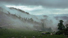 Moody Landscape Scene Of Fog Flowing Through Trees In The Hills