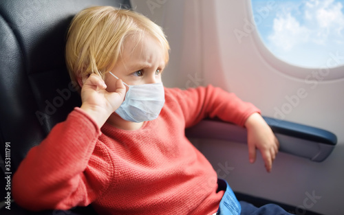 Capricious kid wearing face mask traveling by airplane Fototapeta