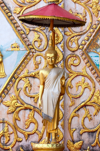 Vertical image Statue of gold  Buddha leela standing with Stucco Laos style on t фототапет