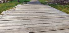 Footbridge Perspective Of Uneven Old Wooden Planks.Platform Part Of Wooden Bridge In A Park. Construction Detail In Natural Environment.