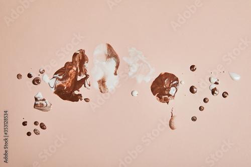 Obraz top view of melted brown and white ice cream on pink background - fototapety do salonu