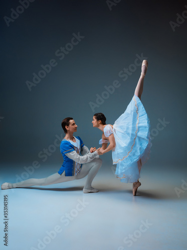 фотография Young and graceful ballet dancers as Cindrella fairytail characters on studio background
