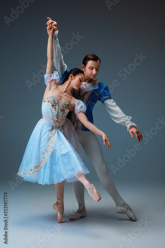Платно Young and graceful ballet dancers as Cindrella fairytail characters on studio background