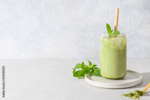 Fototapeta Iced Green matcha tea in glass garnish mint isolated on white table. Space for text. Close up. Horizontal orientation. obraz