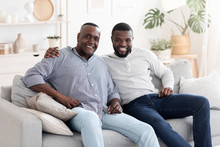 Portrait Of Senior African Man Posing At Home With His Adult Son