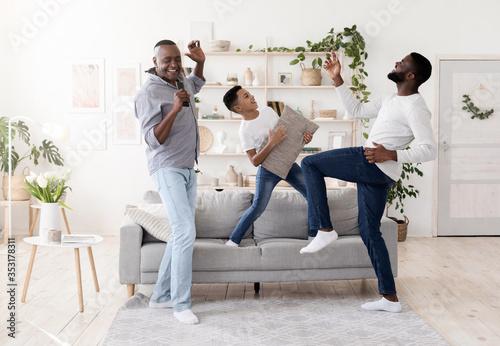 Fototapeta Three generations of men having fun together at home,