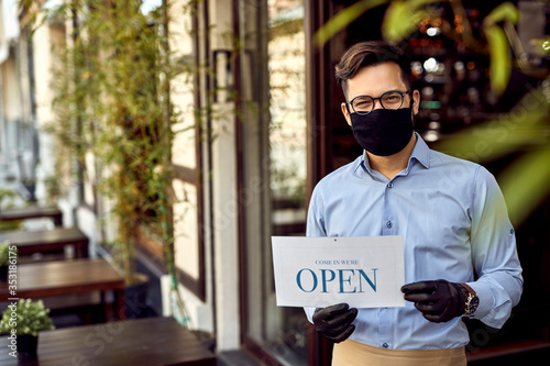 Obraz Happy cafe owner holding open sign while wearing protective face mask. - fototapety do salonu