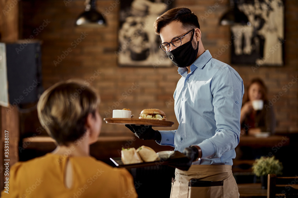 Fototapeta Happy waiter serving food to a guest while wearing protective face mask and gloves in a pub.