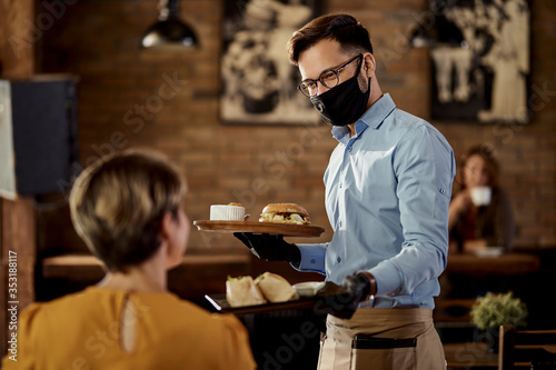 Obraz na płótnie Happy waiter serving food to a guest while wearing protective face mask and gloves in a pub
