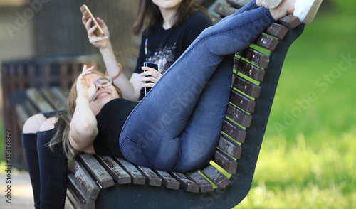 Fotografie, Obraz sexy legs and ass girls in jeans on a bench