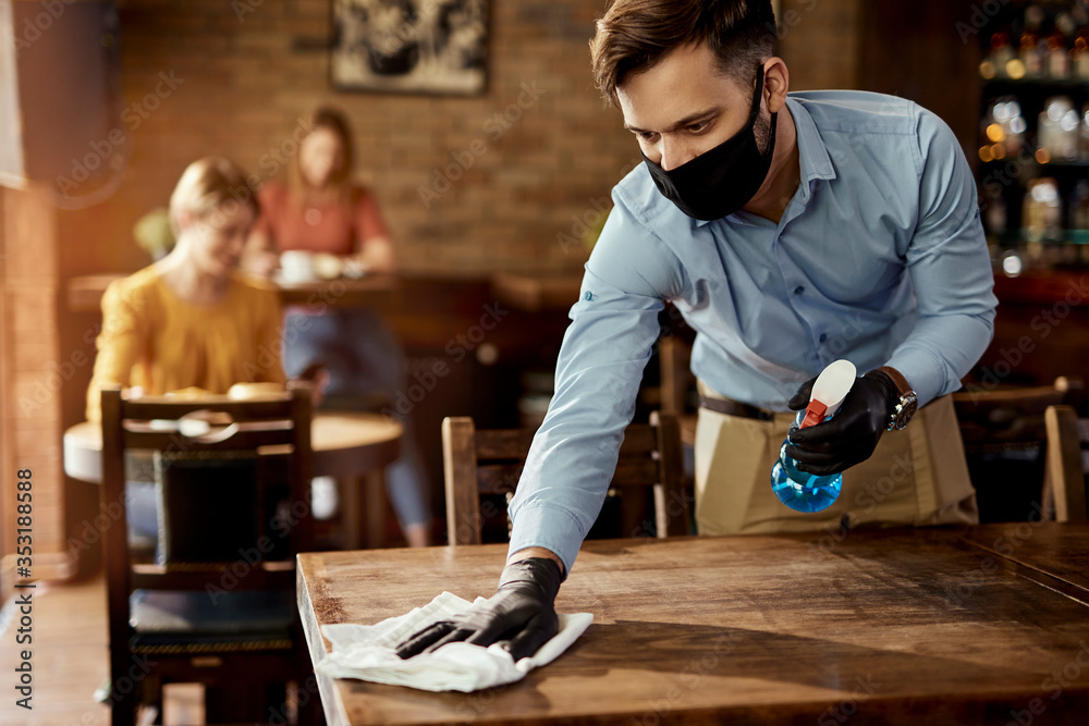 Fototapeta Waiter with protective face mask disinfecting tables in a pub.