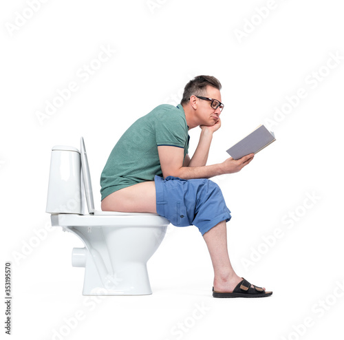 Fotografia, Obraz Man in casual clothes and glasses sits on the toilet and reads book, isolated on white background