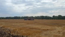 A Tractor Loads Bales Of Hay Onto A Machine After Harvesting On A Wheat Field. Harvesting By Agricultural Machinery.