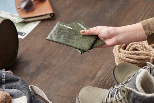 Fototapeta Close-up of unrecognizable woman packing passports when going to travel, hand above wooden table with hiking stuff obraz