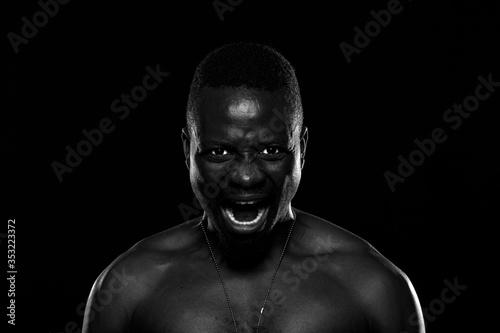 Obraz Hombre negro sobre fondo negro con expresión de furia - fototapety do salonu