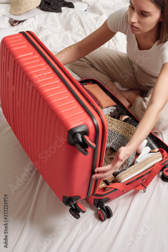 Obraz na plátne Young woman sitting on bed and closing suitcase full of clothes while preparing