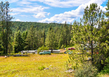 Cars, Trucks And A Mobile Home Are Scattered Throughout The Hillside Land In The North Idaho Mountains.