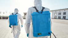 Save Lives. Sanitization And Cleaning Of The City Due To The Emergence Of The Covid19 Virus. Specialized Team In Protective Suits And Masks With Backpack Of Pressurized Spray Disinfectant