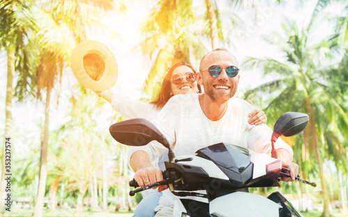 Fototapeta Laughing happy couple travelers riding motorbike during their tropical vacation in Thailand under palm trees. Woman raised hands up with hat. obraz na płótnie