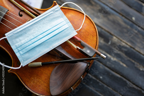 Obraz A face mask on an acoustic violin or viola with a pencil and a bow next to it representing performance restrictions during a pandemic - fototapety do salonu