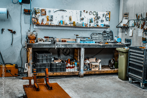 Fotografia, Obraz Garage, service zone for disassembling, repairing motorcycles, station for technical servicing vehicle Inside workshop with large workbench, large number of tools for machining