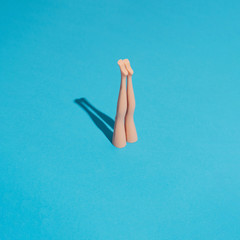 Minimal composition with doll legs and blue background. Sun and sharp shadows. Summer pool or sea diving concept. Vacation and relax inspiration.
