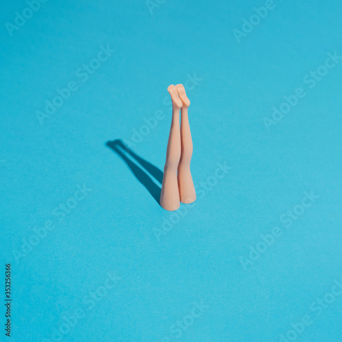 Fotografía Minimal composition with doll legs and blue background