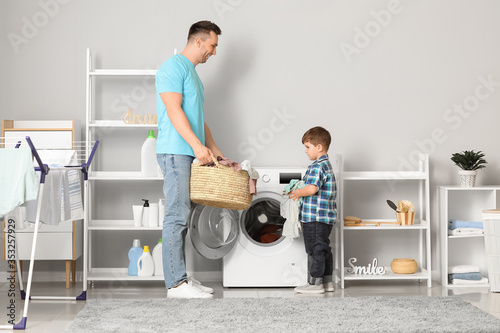 Foto Man and his little son doing laundry at home