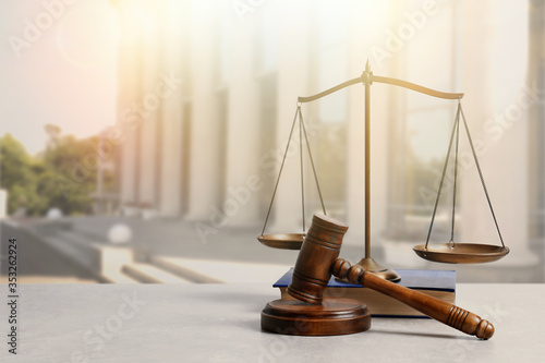 Wooden gavel, scales of justice and book on table against beautiful cityscape, s Wallpaper Mural