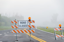 Street Closure Signs In Front Of Foggy Road