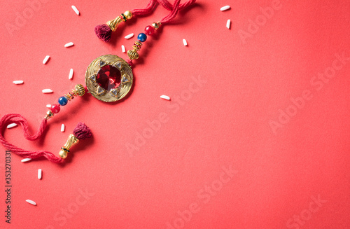 Fotografía Raksha Bandhan, Indian festival with beautiful Rakhi and  Rice Grains on red background
