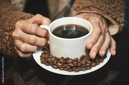 Manos de mujer adulta agarrando una taza de cafe caliente con granos tostados alrededor sobre un plato y fondo negro Canvas Print