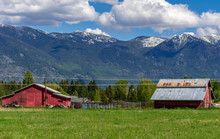 Barns Against A Snow Capped Mountain