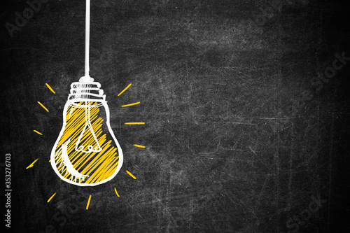 Light bulb drawing as symbol of idea on chalkboard Fototapeta