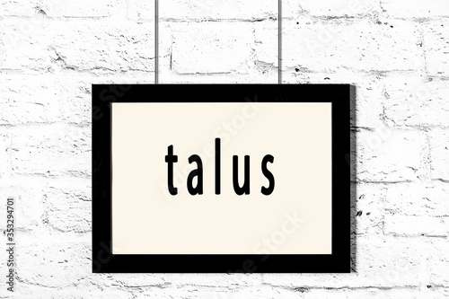 Black frame hanging on white brick wall with inscription talus Canvas Print