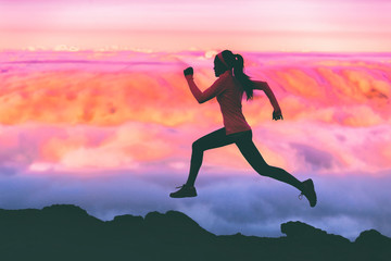 Trail running woman athlete runner exercising in mountains landscape background at sunset with pink color sky clouds.