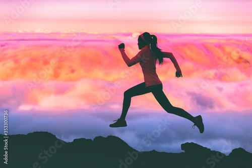 Fototapeta Trail running woman athlete runner exercising in mountains landscape background at sunset with pink color sky clouds. obraz