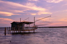 Amazing Fishing Hut In Sunset With Slk Effect Sea In Piallassa Della Baiona, Ravenna, Italy. Sky With Yellow Clouds And Windy Time