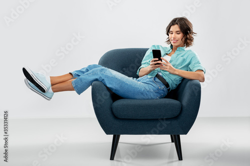 Fotografia people and technology concept - portrait of happy smiling young woman in turquoi