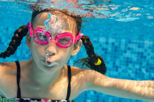 Child Swims In Pool Underwater, Happy Active Girl Dives And Has Fun In Water, Kid Fitness And Sport On Family Vacation