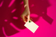 Leinwandbild Motiv Female hand holding blank businesscard. Creative photo with shadow