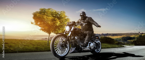 Fotografia fat biker on a bobber motorcycle greeting while riding the empty road on a count