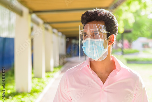 Face of young Indian businessman with mask and face shield thinking at the park Fototapete